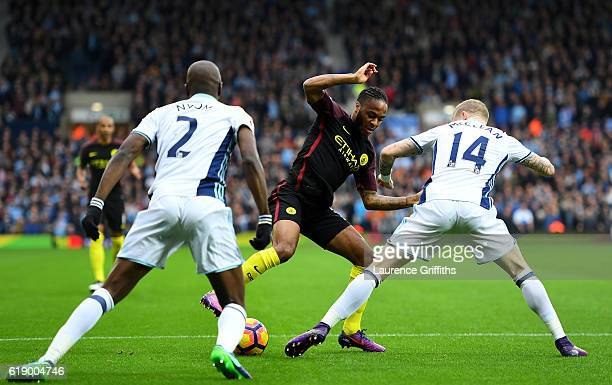 Raheem Sterling of Manchester City controls the ball against Allan Nyom and James McClean of West Bromwich Albion during the Premier League match...