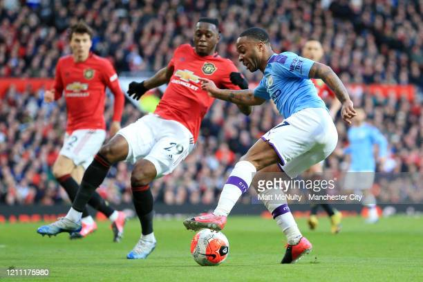 Raheem Sterling of Manchester City controls the ball as Aaron WanBissaka of Manchester United looks on during the Premier League match between...