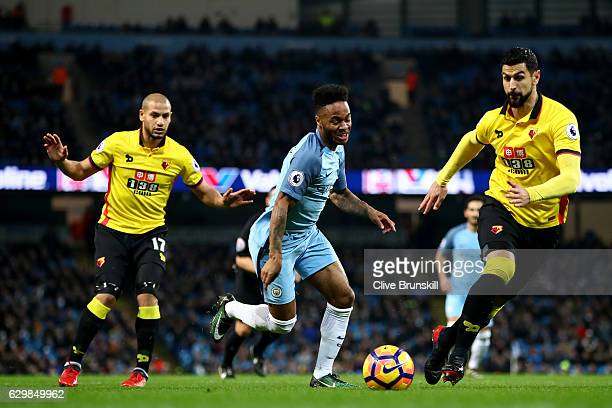 Raheem Sterling of Manchester City controls the ball under pressure of Adlene Guedioura and Miguel Britos of Watford during the Premier League match...