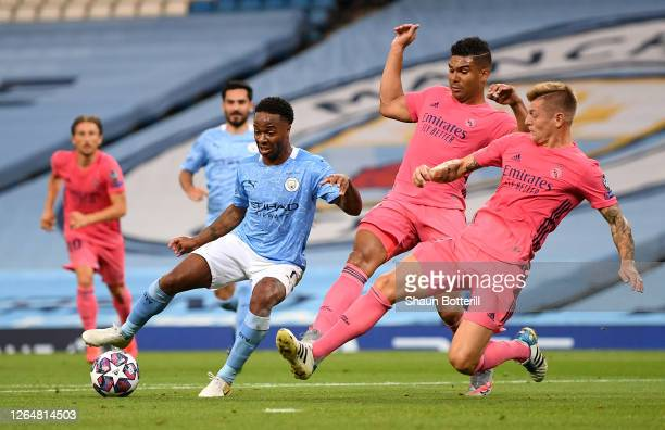 Raheem Sterling of Manchester City is challenged by Casemiro and Toni Kroos of Real Madrid during the UEFA Champions League round of 16 second leg...