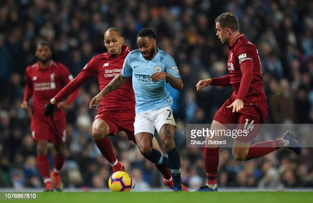 Raheem Sterling of Manchester City is challenged by Fabinho of Liverpool and Jordan Henderson of Liverpool during the Premier League match between...