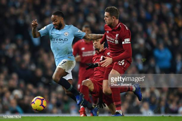 Raheem Sterling of Manchester City is challenged by Jordan Henderson of Liverpool during the Premier League match between Manchester City and...