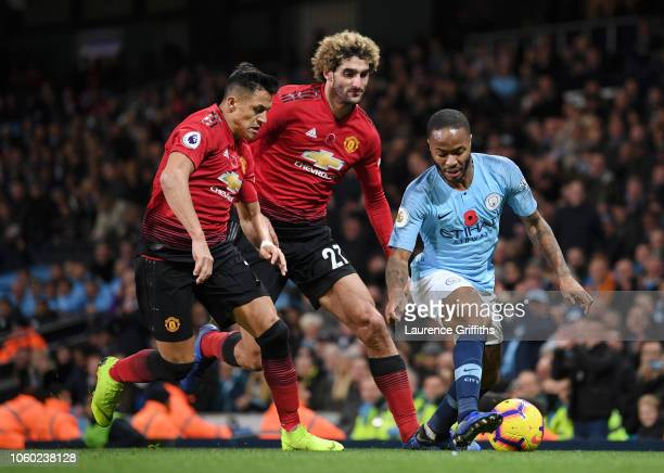 Raheem Sterling of Manchester City is challenged by Marouane Fellaini of Manchester United and Alexis Sanchez of Manchester United during the Premier...