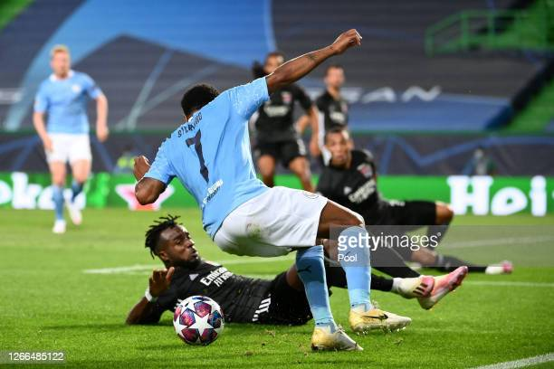 Raheem Sterling of Manchester City is challenged by Maxwel Cornet of Olympique Lyon during the UEFA Champions League Quarter Final match between...