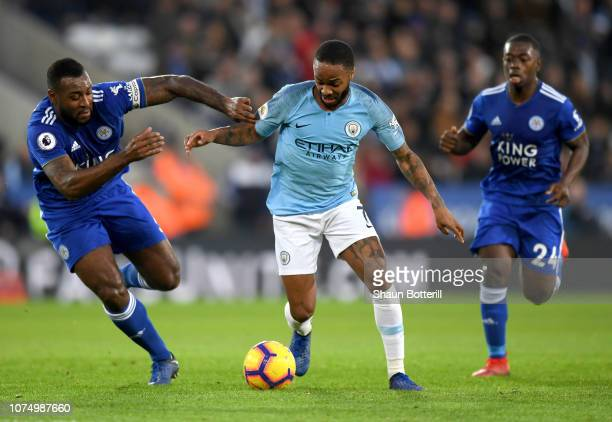 Raheem Sterling of Manchester City is challenged by Wes Morgan of Leicester City during the Premier League match between Leicester City and...