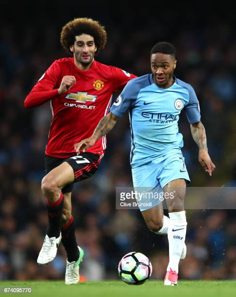 Raheem Sterling of Manchester City is chased down by Marouane Fellaini of Manchester United during the Premier League match between Manchester City...