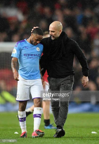 Raheem Sterling of Manchester City is comforted by Pep Guardiola Manager of Manchester City after the Premier League match between Manchester United...