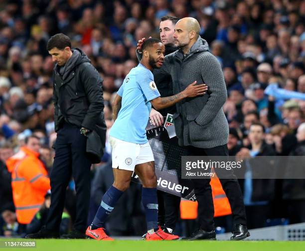 Raheem Sterling of Manchester City is congratulated by Josep Guardiola Manager of Manchester City as he is substituted during the Premier League...