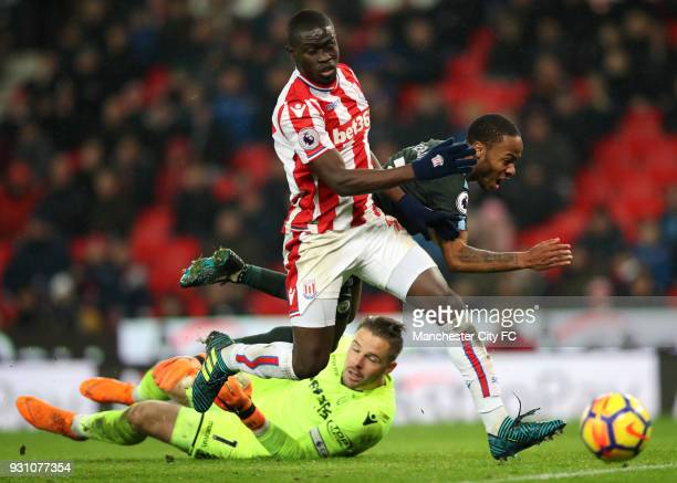 Raheem Sterling of Manchester City is foiled by Badou Ndiaye and Jack Butland of Stoke City during the Premier League match between Stoke City and...