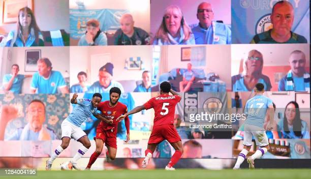 Raheem Sterling of Manchester City is fouled in the penalty area by Joe Gomez of Liverpool as fans watch on the big screen during the Premier League...