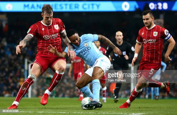 Raheem Sterling of Manchester City is marshalled by Aden Flint and Bailey Wright of Bristol City during the Carabao Cup SemiFinal First Leg match...
