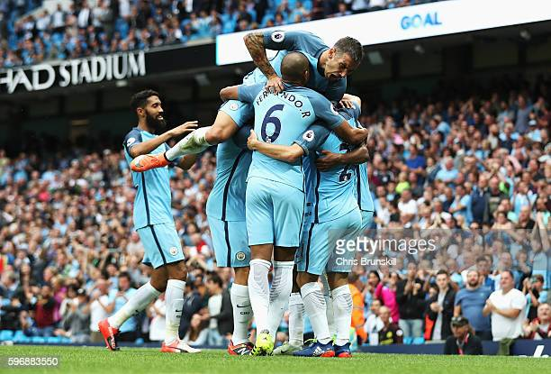 Raheem Sterling of Manchester City is mobbed by team mates including Aleksander Kolorov after scoring his second goal and his team's third during the...