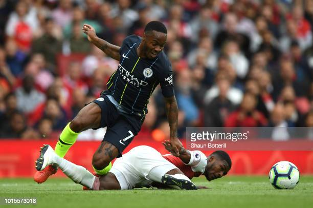 Raheem Sterling of Manchester City is tackled by Ainsley MaitlandNiles of Arsenal during the Premier League match between Arsenal FC and Manchester...