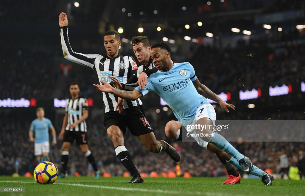 Raheem Sterling of Manchester City is tackled by Javi Manquillo and Isaac Hayden of Newcastle Unitedduring the Premier League match between Manchester City and Newcastle United at Etihad Stadium on January 20, 2018 in Manchester, England.