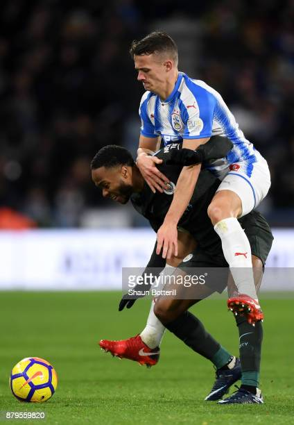 Raheem Sterling of Manchester City is tackled by Jonathan Hogg of Huddersfield Town during the Premier League match between Huddersfield Town and...
