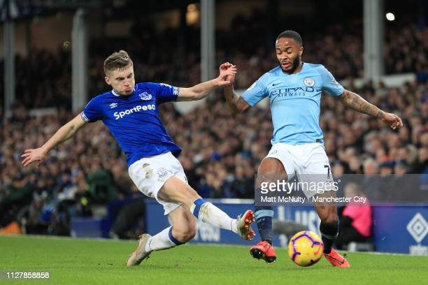 Raheem Sterling of Manchester City is tackled by Jonjoe Kenny of Everton during the Premier League match between Everton FC and Manchester City at...
