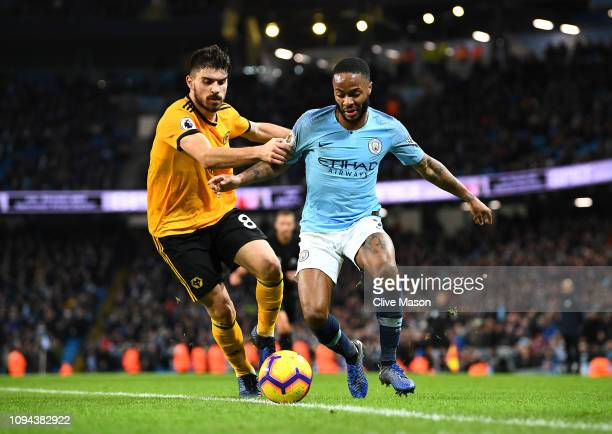 Raheem Sterling of Manchester City is tackled by Ruben Neves of Wolverhampton Wanderers during the Premier League match between Manchester City and...