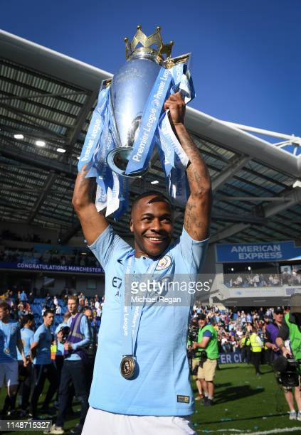 Raheem Sterling of Manchester City poses with the Premier League trophy during the Premier League match between Brighton Hove Albion and Manchester...