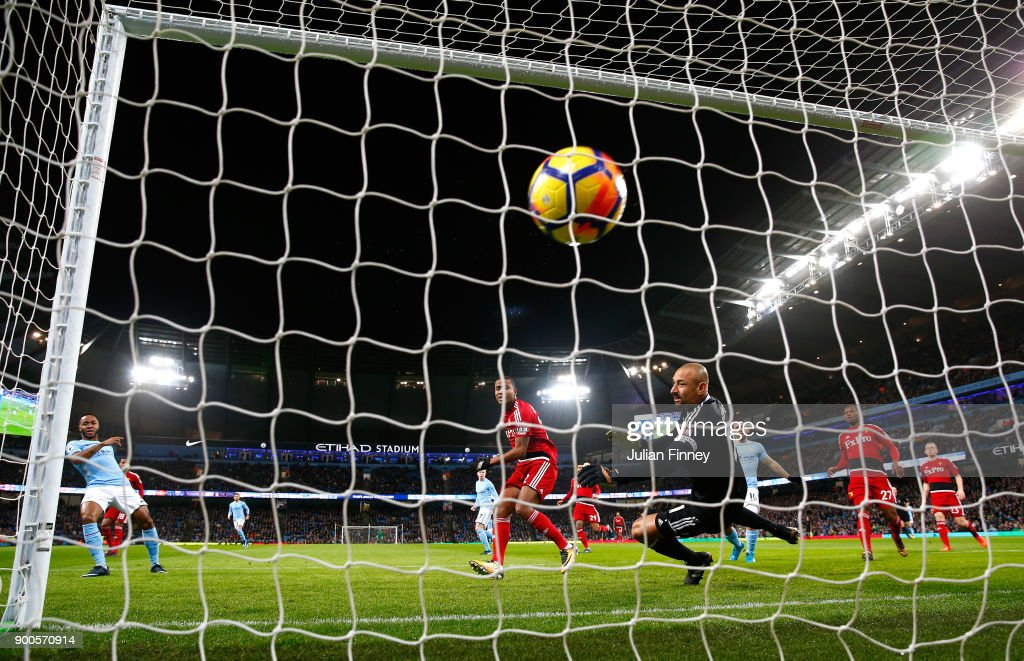 Raheem Sterling of Manchester City scores his sides first goal past Heurelho Gomes of Watford during the Premier League match between Manchester City and Watford at Etihad Stadium on January 2, 2018 in Manchester, England.