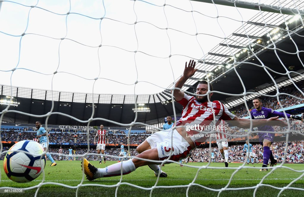 Raheem Sterling of Manchester City scores his sides second goal as Erik Pieters of Stoke City attempts to clear off the line during the Premier League match between Manchester City and Stoke City at Etihad Stadium on October 14, 2017 in Manchester, England.