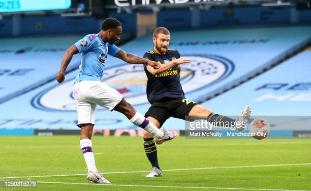 Raheem Sterling of Manchester City scores his team's first goal is challenged by Shkodran Mustafi of Arsenal during the Premier League match between...
