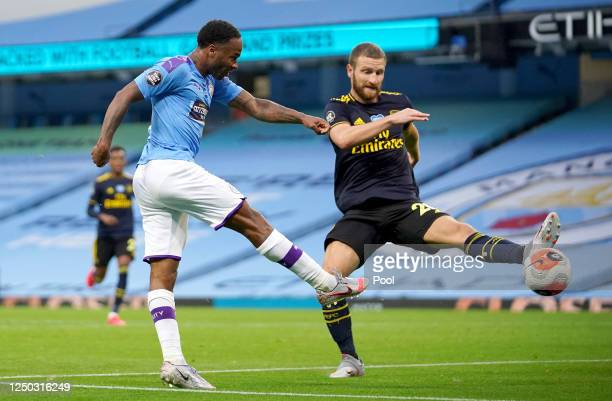 Raheem Sterling of Manchester City scores his team's first goal under pressure from Shkodran Mustafi of Arsenal during the Premier League match...