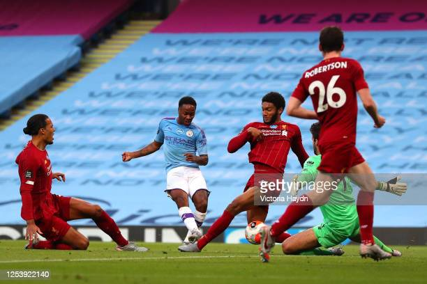 Raheem Sterling of Manchester City scores his team's second goal past Alisson Becker of Liverpool as he is challenged by Joe Gomez of Liverpool...