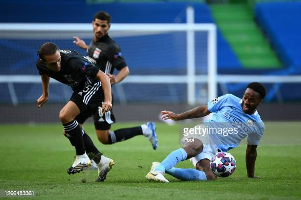 Raheem Sterling of Manchester City tackles Maxence Caqueret of Olympique Lyon during the UEFA Champions League Quarter Final match between Manchester...