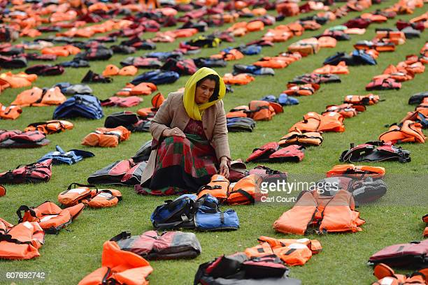 Rahela Sidiqi a trustee of Women for Refugee Women and originally from Afghanistan poses for a photograph among lifejackets that have been used by...