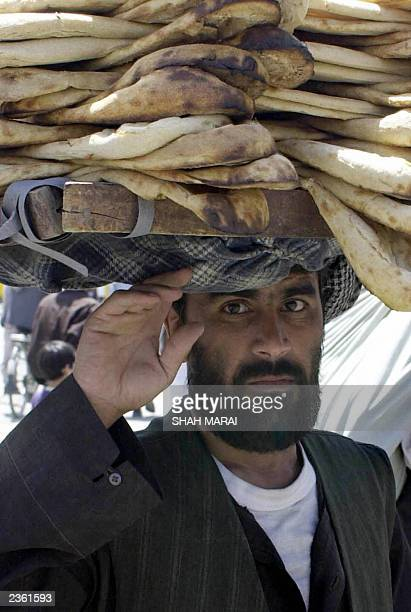 Rahim an Afghan man carries local bread which he hopes to sell at a market in Kabul 31 July 2003 With few employment opportunities in Afghanistan...