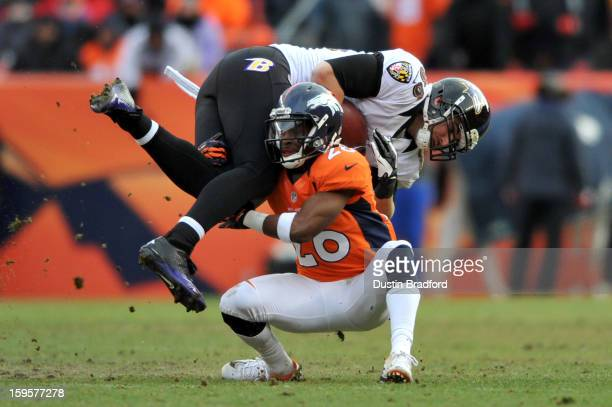 Rahim Moore of the Denver Broncos tackles Dennis Pitta of the Baltimore Ravens during the AFC Divisional Playoff Game at Sports Authority Field at...