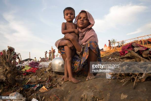Rahima Begum holds her daughter Taslima 4 years old as they wait to be relocated to another camp September 25 2017 in Thainkhali camp Cox's Bazar...