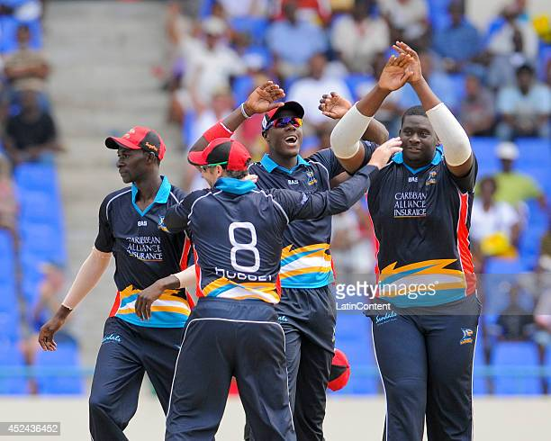 Rahkeem Cornwall of Antigua Hawksbills celebrates with Carlos Brathwaite and teammates the wicket of Kennar Lewis of The Red Steel during a match...