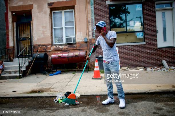 RJ Rahman speaks on the phone while sweeping the street and wearing a wet rag atop his head to cool off on July 20 2019 in Philadelphia PA With heat...