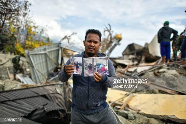TOPSHOT Rahmat Raidi shows portraits of his missing family members at Perumnas Balaroa village in Palu in Indonesia's Central Sulawesi on October 6...