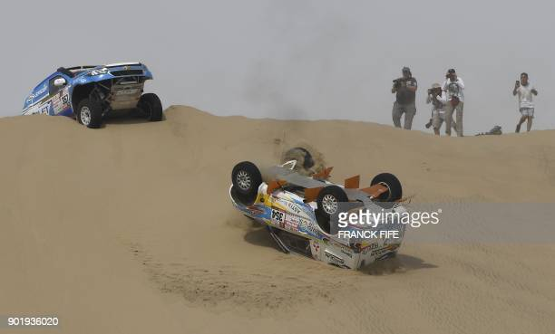 DKR Raid Service's Spanish driver Cristina Gutierrez Herrero and her codriver Gabriel Moiset Ferrer's Mitsubishi ends upside down after crashing...