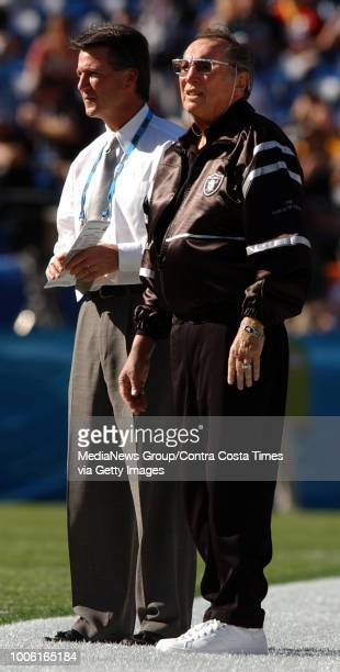 Raider owner Al Davis stands on the sidelines with an unidentified man before the start of Super Bowl XXXVII between the Oakland Raiders and the...