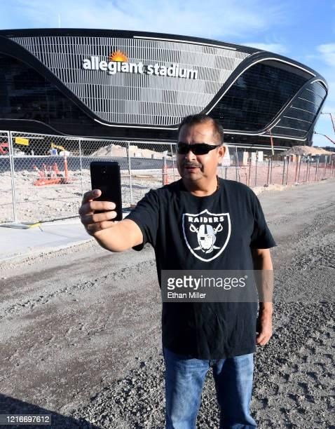 Raiders fan Elias Berra of Nevada takes a selfie in front of Allegiant Stadium the USD 2 billion glassdomed future home of the Las Vegas Raiders on...