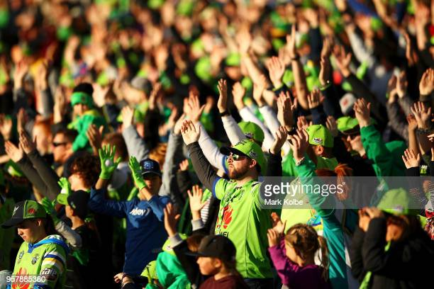 Raiders fans perform the Viking Clap as their team take the field during the round 10 NRL match between the Canberra Raiders and the Cronulla Sharks...