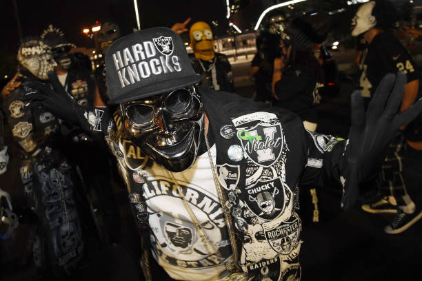 Raiders fans pose as they gather in a parking lot outside Allegiant Stadium, the USD 2 billion 000-seat home of the Las Vegas Raiders, on September...