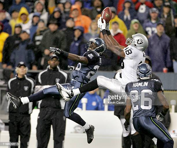 Raiders Randy Moss tries to hold onto the ball as Seahawks Marcus Trufant and Ken Hamlin are there on the defensive coverage of the NFL Monday Night...
