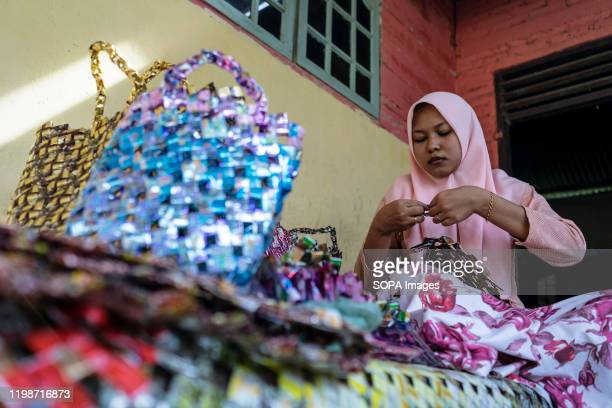 Raihanul Ulfa making the craft bags. Raihanul Ulfa, 24 years old makes craft bags at her home in keude krueng from plastic packaging waste collected...
