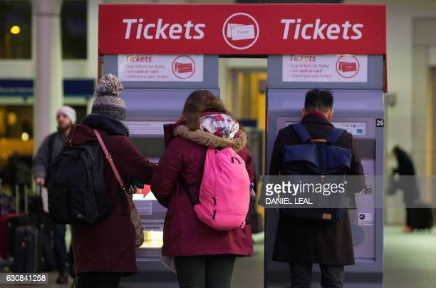 Rail commuters use electronic ticket machines on the concourse at King's Cross railway station in London on January 3 2017 The average price of a...