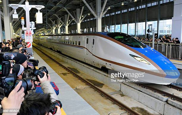 Rail fans take photographs of the first train of the new Hokuriku Shinkansen bullet train at Toyama Station on March 14 2015 in Toyama Japan A string...