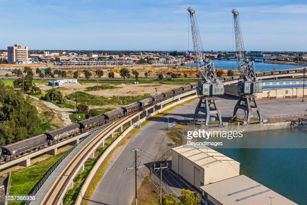 rail freight grain cars crossing port river bridge, new development in background - adelaide stock pictures, royalty-free photos & images