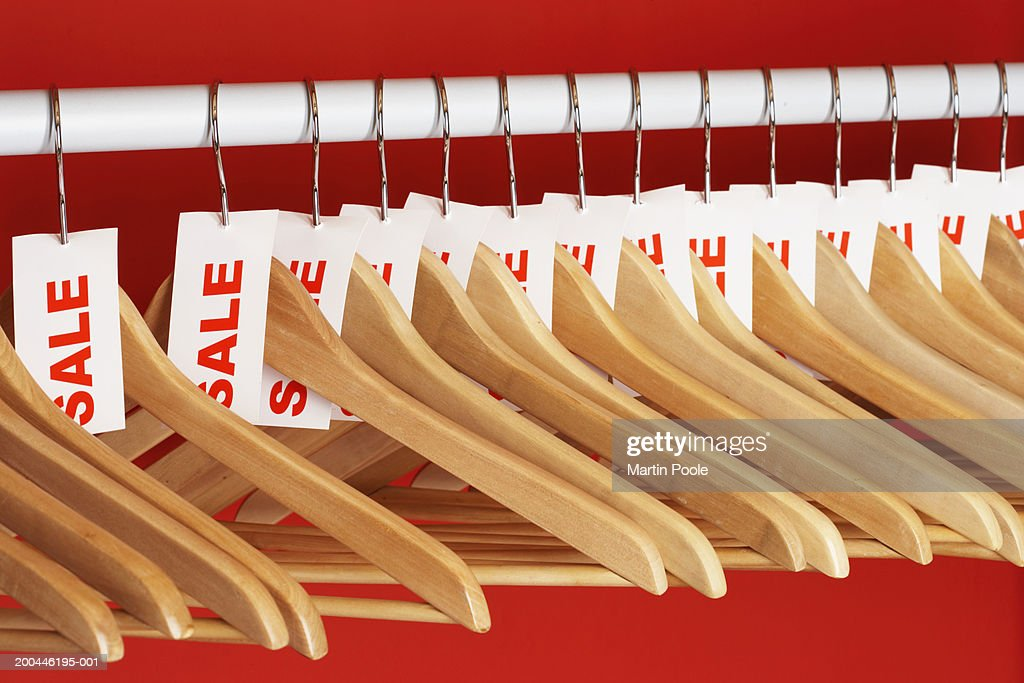 Rail of clothes hangers with sale tags attached, close-up : Foto de stock