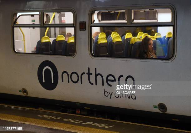 Rail passengers commute on a Northern train, operated by Arriva, a unit of Germany's Deutsche Bahn, as it passes through the train station in...