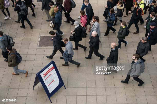 Rail passengers make their way through Manchester Victoria train station during a reduced transport service due to industrial action taken by the RMT...