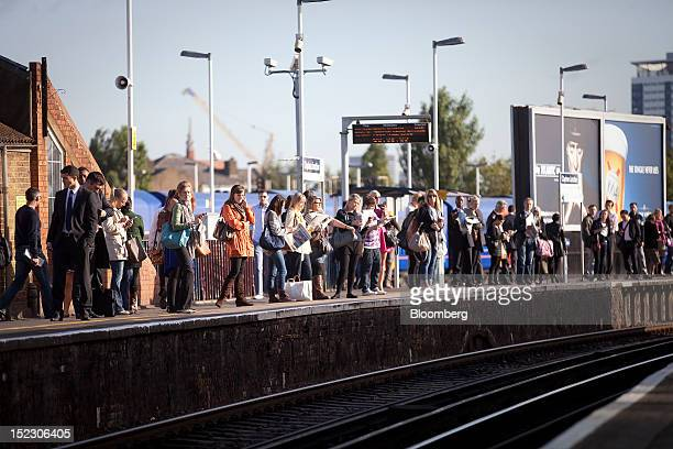 Rail passengers stand and wait for a train on a platform at Clapham Junction railway station in London UK on Tuesday Sept 18 2012 UK rail fares will...