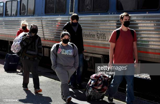 Rail passengers wearing face masks walk on the platform after exiting a train at the Orlando Amtrak station on the first day that the Transportation...